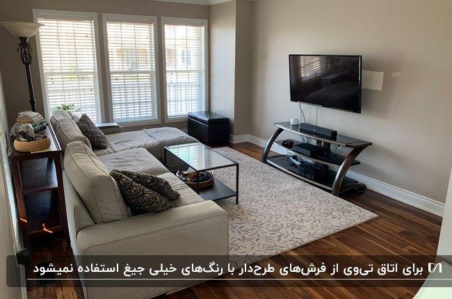 تصویر یک اتاق تلویزیون با با مبل ال شکل کرم، فرش طوسی و کفپوش پارکت
