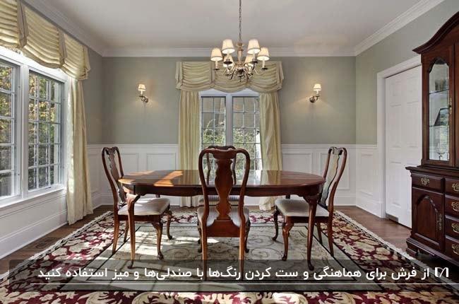 اتاق غذاخوری بزرگی با میز گرد و صندلی های چوبی روی فرش طرحدار اصیل زرشکی و کرم