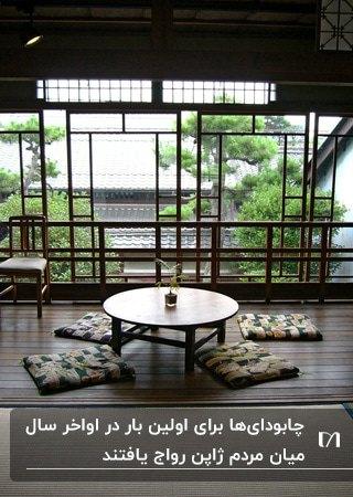 میز ناهارخوری ژاپنی گرد با کوسن های طرحدار کنار دیوار شیشه ای
