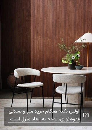 میز گرد و صندلی های سفید قهوه خوری مقابل دیوارپوش چوبی