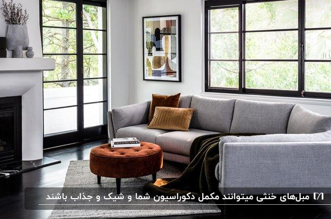 نشیمنی با درب و پنجره شیشه ای بزرگ با فریم مشکی و مبل طوسی با پاف و کوسن قهوه ای