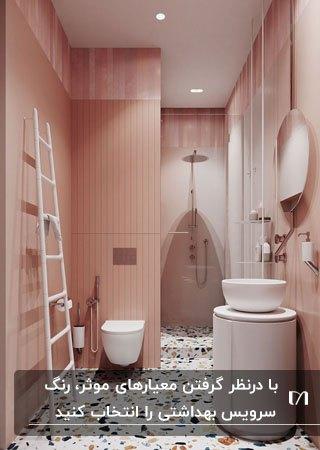 تصویر یک سرویس بهداشتی صورتی با روشویی، کابینت روشویی، توالت فرنگی و نردبان سفید