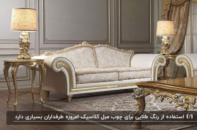 مبلمان کلاسیک طلایی با روکش سفید طرحدار با میزهای طلایی و دو آباژور طلایی