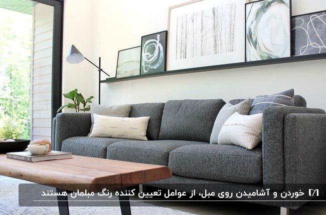 تصویر نشیمنی با مبلمان خاکستری و میز عسلی چوبی وقاب های روی دیوار