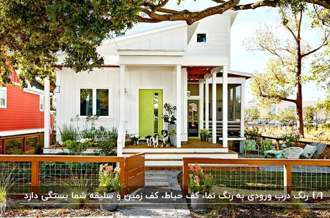 خانه ای با نمای سفید، درب ورودی سبز فسفری، حفاظ و پله و سقف چوبی
