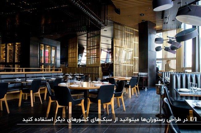 طراحی داخلی رستورانی با دکوراسیون مشکی و طلایی با لوسترهای آویز