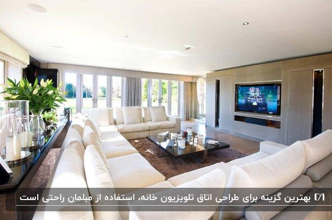 اتاق تلویزیون با دیوار شیشه ای و مبلمان یو شکل سفید رنگ