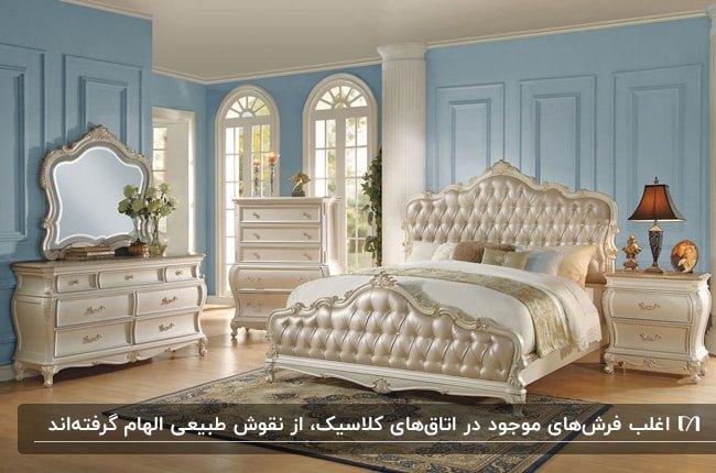 اتاق خوابی به سبک کلاسیک با دیوارهای آبی، تخت، دراور، کنسول و پاتختی کرم براق