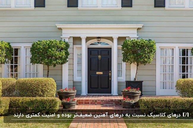 خانه ای با نمای طوسی روشن و فریم درب و پنجره های سفید با درب ورودی کلاسیک قهوه ای