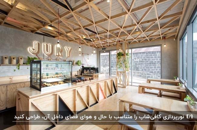 فضای داخلی کافی شاپ با میز و صندلی و کفپوش و سقف چوبی با نورپردازی چراغ های آویز