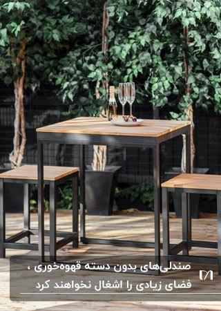 تصویر میز و صندلی های بدون دسته قهوه خوری با فریم فلزی مشکی و صفحه چوبی
