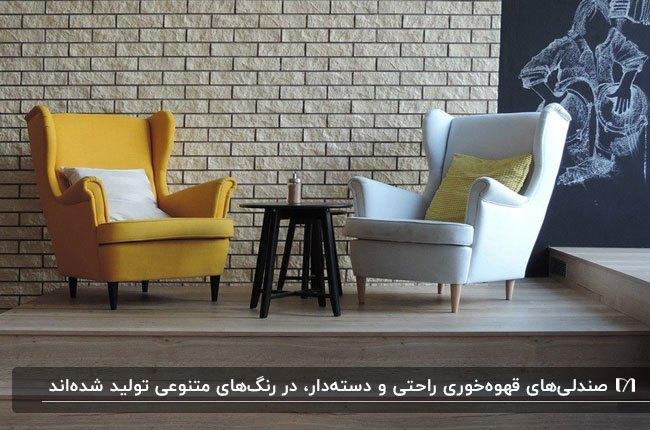 تصویر دو صندلی دسته دار به رنگ های زرد و سفید و میز گرد قهوه خوری مقابل دیواری آجری