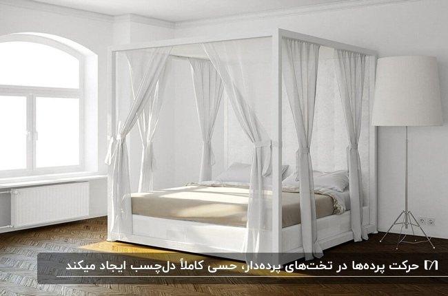 اتاق خوابی با تخت پرده دار سفید با پرده های حریر سفید، آباژور پایه بلند سفید و کفپوش چوبی