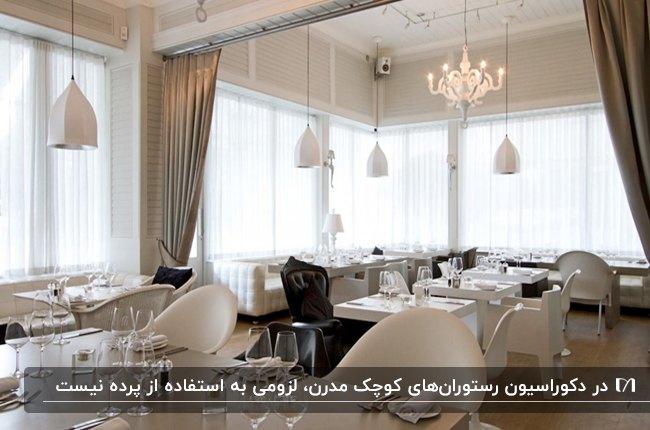 رستورانی بزرگ و کلاسیک با پرده های سفید و قهوه ای و میز وصندلی های سفید ومشکی