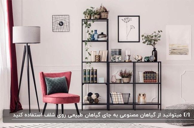 تصویر شلف های طبقه ای مشکی رنگ کنار صندلی صورتی و آباژور پایه بلند با لوازم دکوری