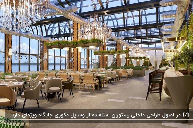 رستورانی با سقف و دیوارهای شیشه ای، میز وصندلی های چوبی و گل و گیاه و لوسترهای کریستالی