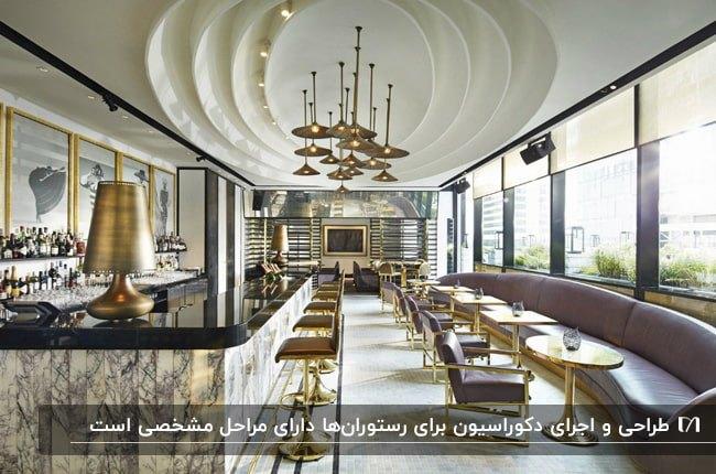 طراحی داخلی رستورانی با یک پنجره سرتاسری و میز، نیمکت و صندلی های بنفش و طلایی و سقف کاذب بیضی شکل