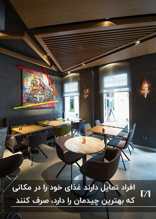 رستورانی با میزهای چوبی و صندلی های مشکی با طراحی سقف چوبی مثلثی