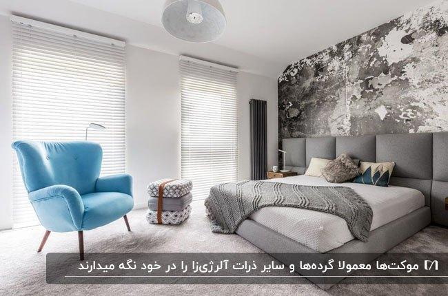 اتاق خوابی با کاغذدیواری طوسی پشت تخت خواب طوسی، مبل آبی و موکت طوسی روشن