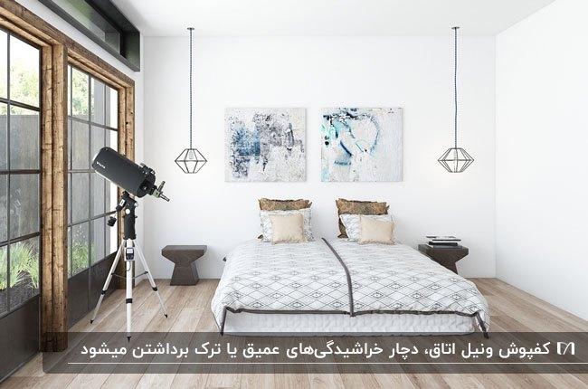 اتاق خوابی با کفپوش وینیل، تخت دو نفره، دو تابلوی نقاشی روی دیوار و دو چراغ آویز اطراف تخت