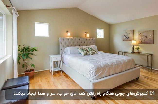 اتاق خوابی با سقف شیروانی، تخت طوسی و کفپوش چوبی