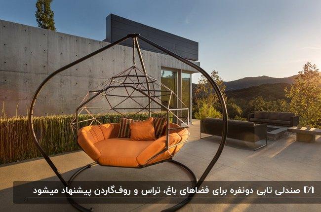 تصویری از یک صندلی ریلکسی پایه دار دو نفره با تشکچه و کوسن های نارنجی و قهوه ای در فضای باز
