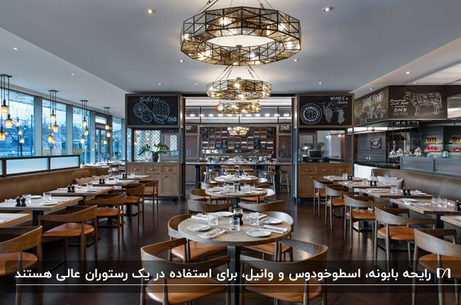 رستوران مدرن کوچکی با میز و صندلی های چوبی با پارچه نارنجی و لوسترهای آویز چندضلعی