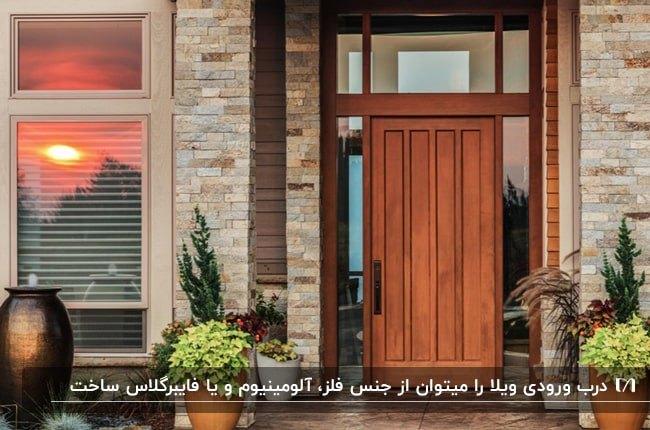 تصویر نمای خارجی آجری کرم رنگ خانه ای با درب ورودی چوبی و گلدان های گل اطراف آن