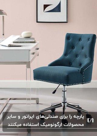 اتاق کاری با دیوارهای صورتی، میزکار سفید و صندلی اداری پارچه ای آبی تیره