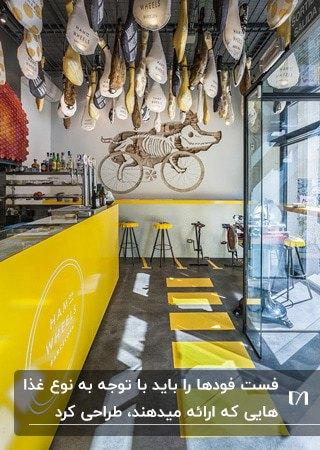 فست فودی با ترکیب رنگ زرد، خاکستری و سفید و استفاده از دوچرخه بلااستفاده روی دیوار