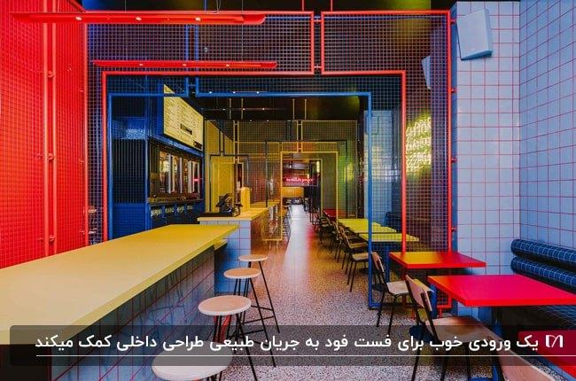 فست فودی با دکوراسیون داخلی با لوله های فلزی به رنگ آبی، قرمز و چوب