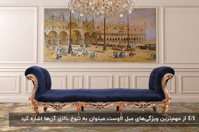 مبل لاوست با فریم منبت کاری شده طلایی و پارچه سرمه ای جلوی تابلوی نقاشی بزرگی روی دیوار سفید