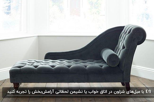تصویر یک مبل شزلون خاکستری با پایه های چوبی و کوسن استوانه ای