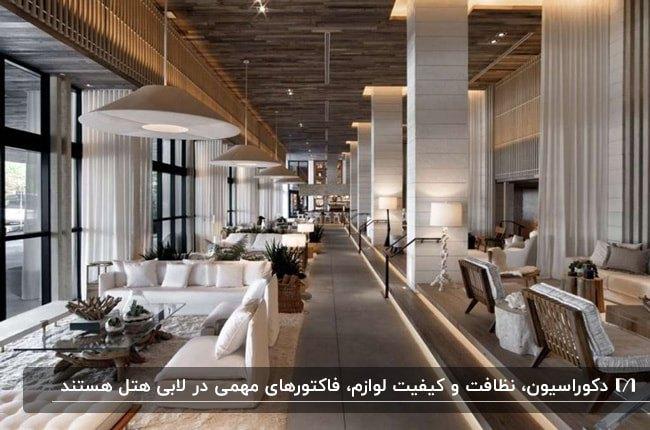تصویر لابی بزرگ یک هتل با مبلمان و میز و صندلی های کرم و قهوه ای و لوستر های آویز