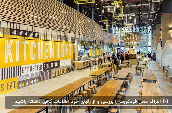 فودکورتی با میزهای مستطیلی و چهارپایه های گرد چوبی با دیوارپوش های زرد
