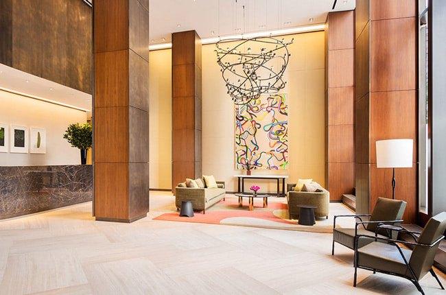لابی شیک با ستون های چوبی،لوستر آویز با شکل هندسی متفاوت و تابلوی نقاشی خطی رنگی روی دیوار