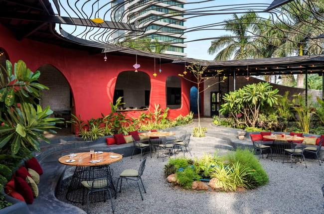 باغ رستورانی با کفپوش سنگ ریزه، میز و صندلی و نیمکت های خاکستری با کوسن ها و دیوار قرمز رنگ