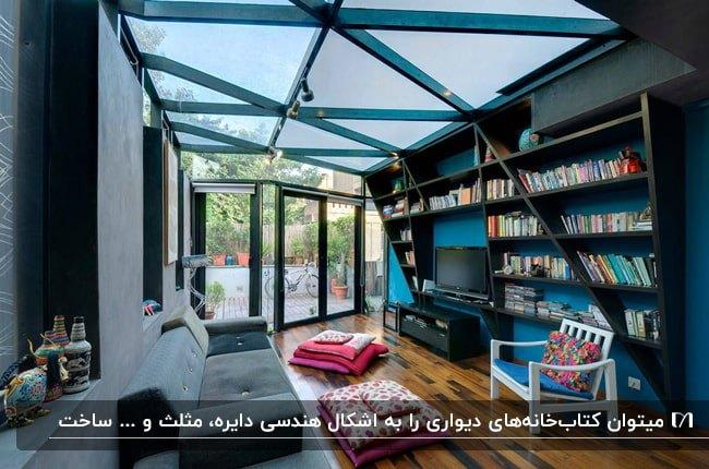 اتاقی با دیوارهای آبی و خاکستری و قفسه های هندسی مشکی برای قرار دادن کتاب مقابل مبل طوسی