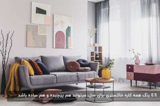 نشیمنی مدرن با مبل خاکستری، کوسن های سرمه ای و زرشکی و خردلی و تابلوهای نقاشی روی دیوار
