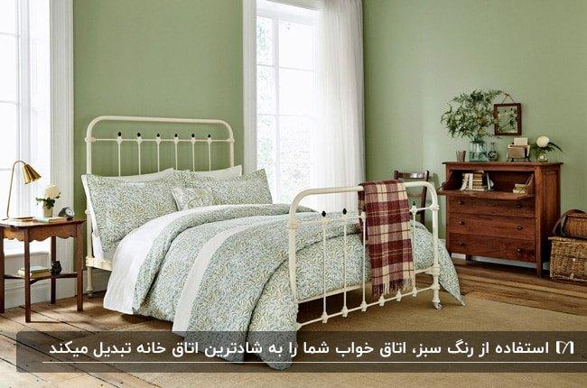 اتاق خوابی با دیوارهای سبز رنگ، تخت سفید و کنسول چوبی