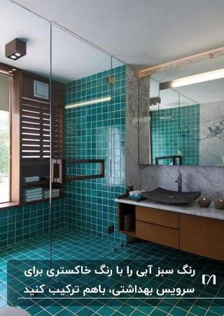 سرویس بهداشتی با کاشی های رنگ طوسی و سبزآبی برای دیوار و روشویی چوبی و آینه مربعی