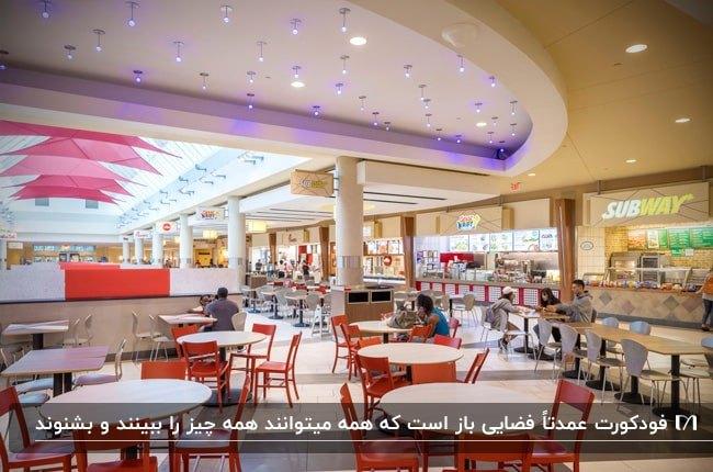 فودکورتی در یک مرکز تجاری با میزهای گرد سفید و صندلی های فلزی نارنجی