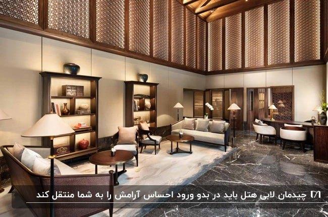 تصویر لابی یک هتل لوکس با تزئینات چوبی، قفسه کتاب و مبلمان کرم با فریم چوبی قهوه ای