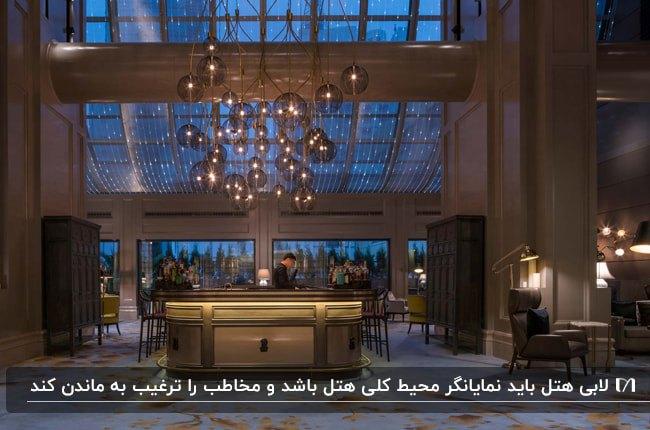 طراحی دکوراسیون داخلی لابی هتلی با دیوارهای خاکستری، سقف شیشه ای و لوستر آویز توپ توپی با میز پذیرش