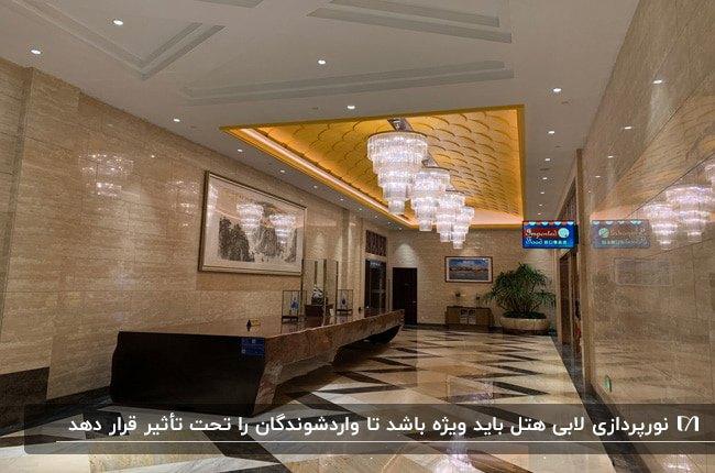 لابی هتلی با میز رسپشن قهوه ای و سقف نورپردازی شده با چهار لوستر کریستالی آویز