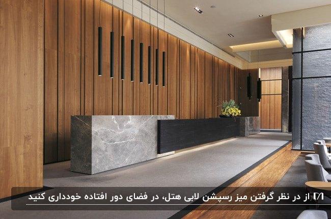 میز رسپشن طوسی و مشکی در لابی هتل با دیوارپوش چوبی و لوستر آویز مشکی