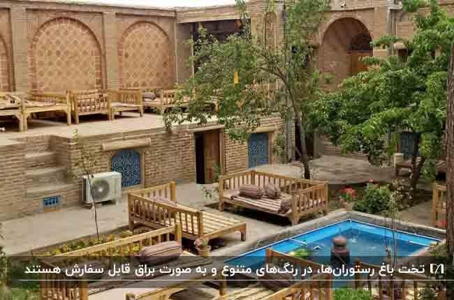 تصویر باغ رستورانی سنتی با دیوارهای آجری و تخت های چوبی
