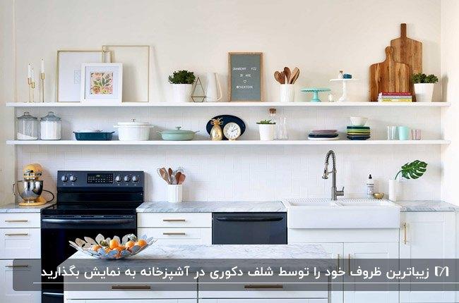 آشپزخانه ای با کابینت سفید و دو شلف سفید بالای سینک ظرفشویی با لوازم دکوری
