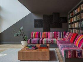 مبلمان ال شکل با پارچه طرحدار سنتی با رنگ های گرم مقابل دیواری به عنوان کتابخانه