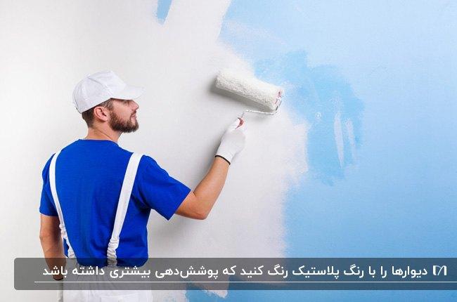 مردی با لباس و کلاه کار در حال زدن رنگ پلاستیک سفید روی دیوار آبی